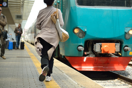 Running woman miss train in railway station.