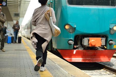 Running woman miss train in railway station.