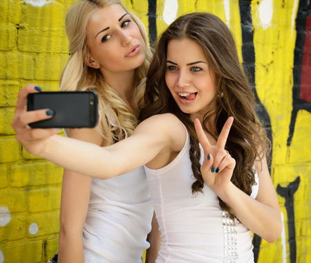 Happy attractive girls with smart phone take selfie against urban grunge graffiti wall. Stock Photo