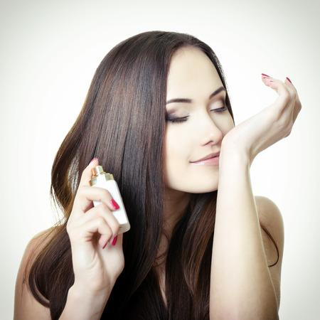 fiatal, gyönyörű nő, kezében egy üveg parfüm és illatú aroma