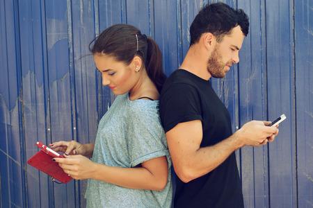 vida social: Pareja joven que toma usando los teléfonos inteligentes. Selfie, las redes sociales, la adicción a internet, amor, amistad, adulto joven, concepto de ocio. Imagen de tonos y ruido añadido. Foto de archivo