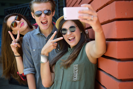 Young girls and boy having fun outdoor and making selfie with smart phone against red brick wall. Urban lifestyle, happiness, joy, friends, social network concept. Image toned and noise added. Stockfoto