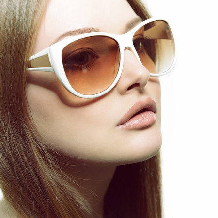 sunglasses isolated: Girl in sunglasses. Beautiful woman in sunglasses posing in studio over white background. Stock Photo