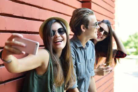 medios de comunicación social: Los jóvenes se divierten al aire libre y hacer selfie con el teléfono inteligente contra la pared de ladrillo rojo. Forma de vida urbana, la felicidad, la alegría, amigos, auto foto concepto de red social. Imagen de tonos y ruido añadido.