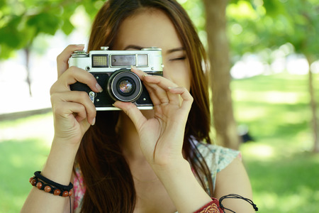 camera girl: Girl taking photo with retro camera outdoor, image toned and noise added. Stock Photo