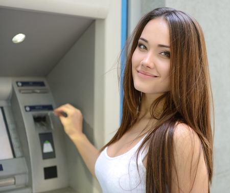 Young happy smiling woman using cash machine