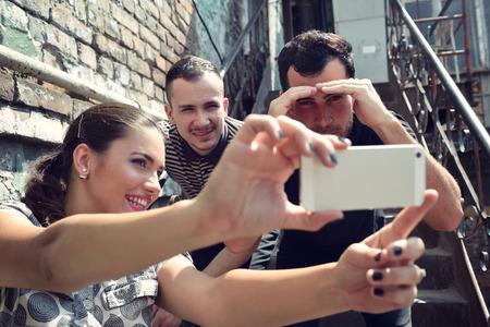 hombre disparando: Amigos felices que toman la foto del uno mismo con el teléfono elegante. Selfie, amistad, adultos jóvenes, la felicidad, el concepto de ocio. Imagen en tonos.