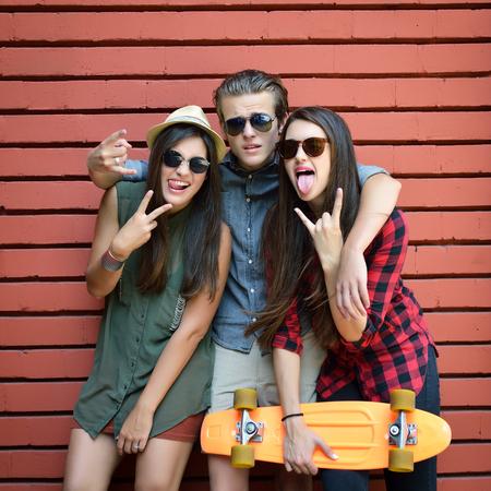 pareja adolescente: Los jóvenes posando con tablero centavo y gafas de sol contra la pared de ladrillo rojo. Forma de vida urbana, la felicidad, la alegría, amigos, adolescente, primero el concepto de amor. Imagen de tonos y ruido añadido.