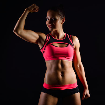 muscular body: Portrait of young fitness woman shows biceps. Muscular female body with sweat. Perfect sportive female body. Sporty girl over black background. Stock Photo