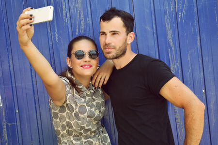 man style: Happy couple taking self photo with smart phone. Selfie, love, relationship, young adult, concept. Image toned.