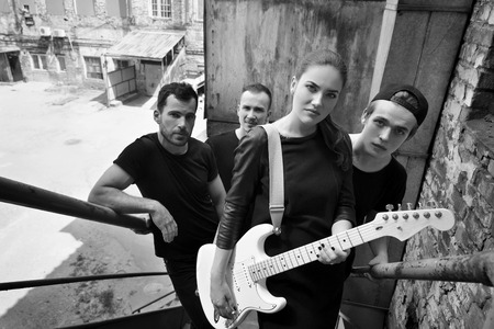 soloist: Music band outdoor portrait. Musicians and woman soloist posing outside against grunge yard, black and white. Stock Photo