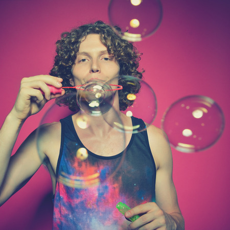 pink bubbles: Young man blowing soap bubbles, studio pink background, image toned.