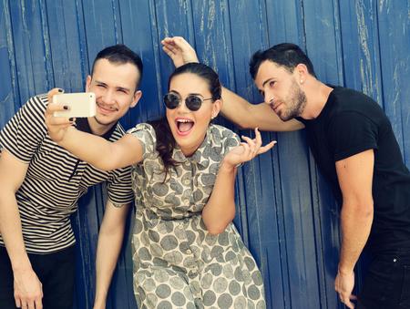 hombre disparando: Amigos felices que toman auto foto con el teléfono inteligente. Selfie, amistad, adulto joven, felicidad, concepto de ocio. Imagen de tonos.