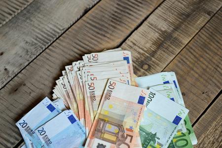 cash money: Euro banknotes. Background with european cash money on wooden background.