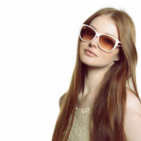 gafas de sol: Muchacha en gafas de sol. Mujer hermosa en gafas de sol posando en estudio sobre fondo blanco.