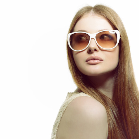 beauty skin: Girl in sunglasses. Beautiful woman in sunglasses posing in studio over white background. Stock Photo