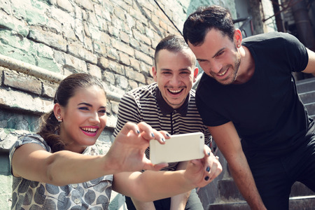 amicizia: Amici che catturano foto auto con smart phone. Selfie, amicizia, giovane adulto, concetto di tempo libero.