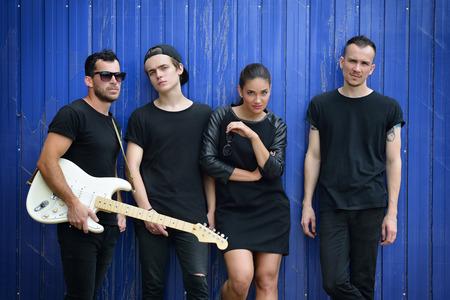音楽バンド、屋外のポートレート。ミュージシャンや女性ソリスト グランジ青いフェンス、トーンのイメージと追加するノイズに対して外ポーズし
