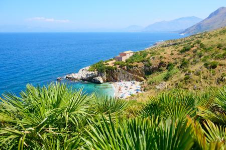 Paesaggio paradiso con spiaggia, mare, montagna, e alberi tropicali, Italia, Sicilia, San Vito Lo Capo. Riserva Naturale dello Zingaro.