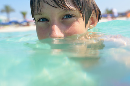 child smile: little boy swimming in sea with clean turquoise water transparent