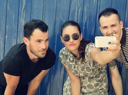 mooie vrouwen: Gelukkige vrienden die zelf foto met slimme telefoon. Selfie, vriendschap, jong volwassen, geluk, vrije tijd concept. Afbeelding afgezwakt.