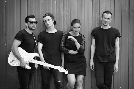 soloist: Music band outdoor portrait. Musicians and woman soloist posing outside against grunge fence, black and white. Stock Photo