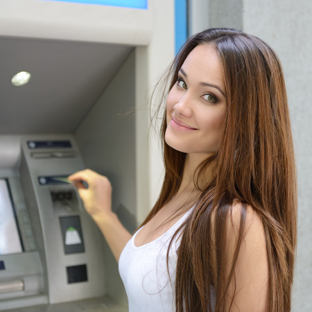 automatic teller machine bank: Young happy smiling woman using cash machine