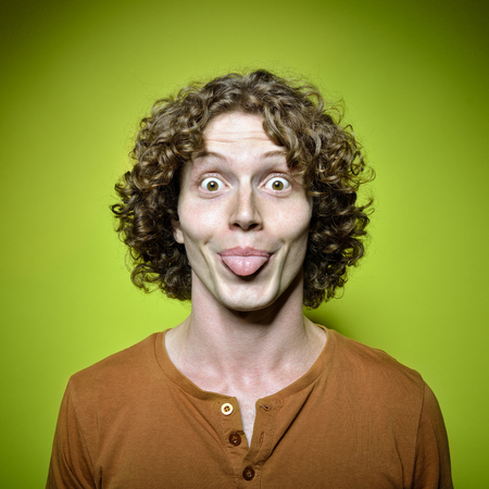 lively: Young funny man shows his tongue, studio shot over green background. Lively face. Image toned and noise added.