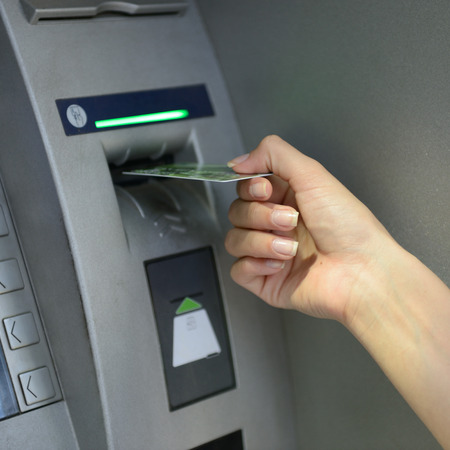 Woman withdrawing money from credit card at ATM. Cash machine.