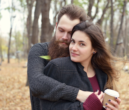 outdoor outside: Fashion portrait of young couple drinking coffee in autumn park outdoor, image toned and noise added. Hipster man with beard and moustache embracing his beautiful girlfriend outside. Stock Photo