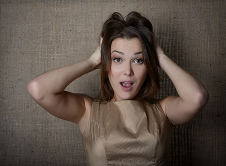 agitated: Portrait of emotional surprised young woman over canvas background.
