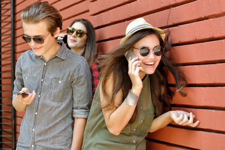 Los jóvenes se divierten al aire libre que usa el adminículo como un teléfono inteligente y la almohadilla contra la pared de ladrillo rojo. estilo de vida urbano, internet y herramienta de la dependencia, los amigos, el concepto de red social. Imagen de tonos y ruido añadido.