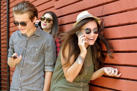 persona feliz: Los jóvenes se divierten al aire libre que usa el adminículo como un teléfono inteligente y la almohadilla contra la pared de ladrillo rojo. estilo de vida urbano, internet y herramienta de la dependencia, los amigos, el concepto de red social. Imagen de tonos y ruido añadido.