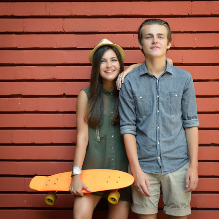 youth group: Young couple posing with penny board summer outdoor against red brick wall. Urban lifestyle, happiness, joy, friends, teenage, first love concept. Image toned and noise added. Stock Photo