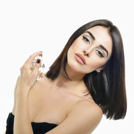 Lady with perfume, young beautiful woman holding bottle of perfume and smelling aroma over white background