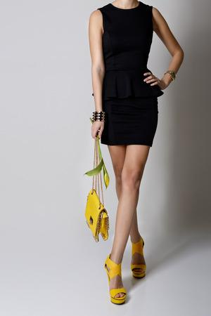 Mode Mädchen. Junge Frau, die im schwarzen Kleid und im gelben handlbag und in den Schuhen aufwirft Standard-Bild