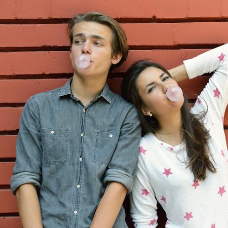 pareja de adolescentes: Pareja joven posando al aire libre que sopla burbujas con goma de mascar contra la pared de ladrillo rojo. Forma de vida urbana, la felicidad, la alegría, amigos, adolescente, primero el concepto de amor. Imagen de tonos y ruido añadido.