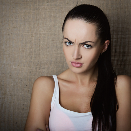 emociones: Portraiot de enojado, mujer joven insatisfecho teje sus cejas sobre el fondo de la lona, ??imagen de tonos.