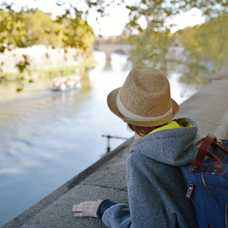 admires: Boy admires the scenery of river Tiber, Rome. Image toned.