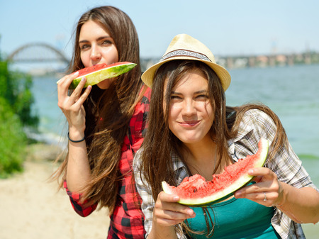 frienship: Happy girls eating watermelon on the beach. Youth lifestyle. Happiness, joy, frienship, holiday, beach, summer concept. Young people having fun outdoor. Stock Photo