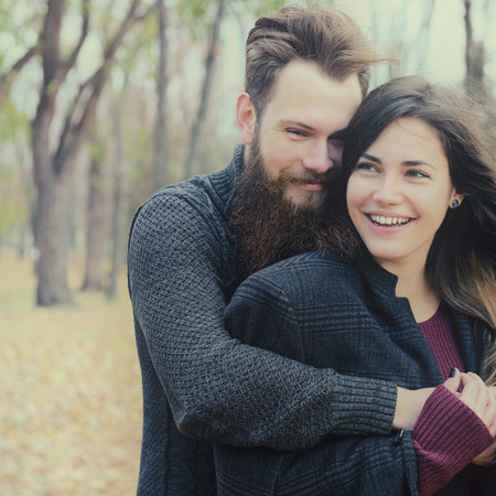 outdoor outside: Fashion portrait of young couple have fun in autumn park outdoor, image toned and noise added. Hipster man with beard and moustache embracing his beautiful happy smiling girlfriend outside.