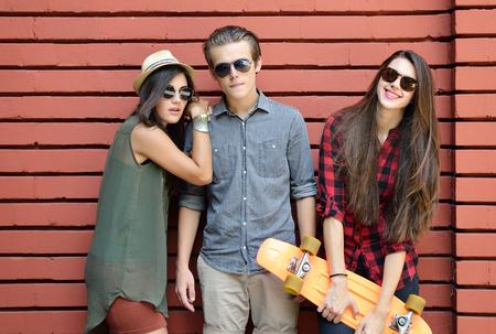 jolie fille: Jeunes amis posant avec planche de penny extérieure d'été contre le mur de briques rouges. mode de vie urbain, le bonheur, la joie, amis, adolescent, premier concept de l'amour. Image teintée et le bruit ajouté.
