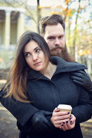 women coffee: Fashion portrait of young couple drinking coffee in autumn park outdoor, image toned and noise added. Hipster man with beard and moustache embracing his beautiful happy smiling girlfriend outside.