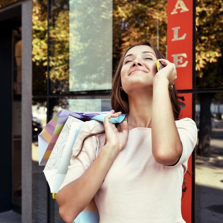fashionable woman: Beautiful young fashion woman with shopping bags near shop window calling smart phone