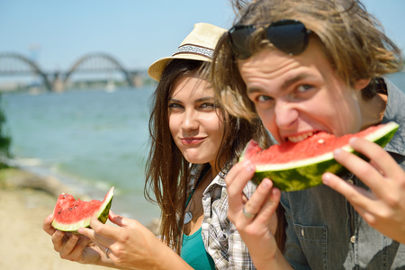 summer fruit: Happy friends eating watermelon on the beach. Youth lifestyle. Happiness, joy, frienship, holiday, beach, summer concept. Group of young people having fun outdoor.