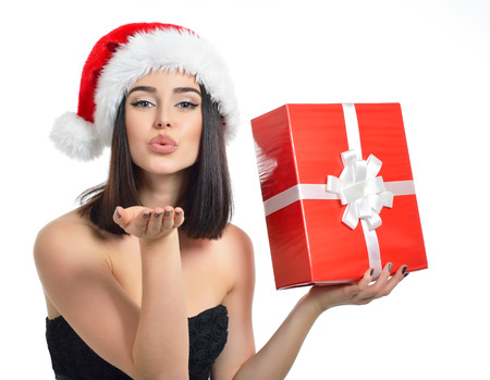 red gift box: Christmas girl. Beautiful x-mas woman holding gift box and sending wind kiss over white background.