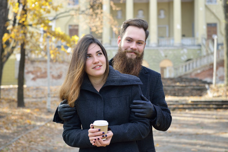 outdoor outside: Fashion portrait of young couple drinking coffee in autumn park outdoor, image toned and noise added. Hipster man with beard and moustache embracing his beautiful happy smiling girlfriend outside.