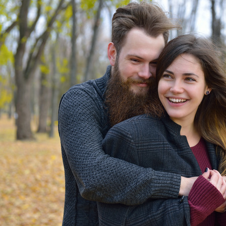 outdoor outside: Fashion portrait of young couple in autumn park outdoor, image toned and noise added. Hipster man with beard and moustache embracing his beautiful happy smiling girlfriend outside.