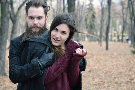 outdoor outside: Fashion portrait of young couple are in autumn park outdoor, image toned and noise added. Hipster man with beard and moustache embracing his beautiful happy smiling girlfriend outside. Stock Photo