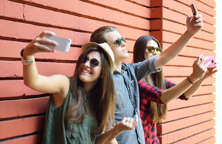 I giovani di divertimento all'aria aperta e facendo selfie con il telefono astuto contro muro di mattoni rossi. Stile di vita urbano, felicità, gioia, amici, foto auto concetto di rete sociale. Immagine tonica e il rumore aggiunto.